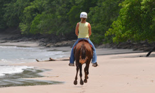Lady during a horseback ride on the beach